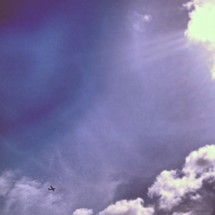 Plane flying across blue sky with cloud formations and sun beams.
