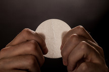 Hands breaking a communion wafer.