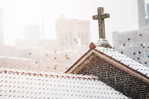 pigeons flying of a church roof covered in snow