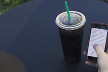 a man looking at a cellphone screen and iced soda