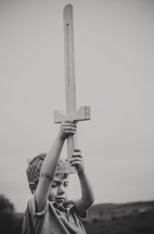 a boy in a crown holding up a wooden sword