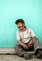 An elderly man sitting on a sidewalk