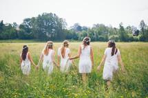 bridesmaids walking hand in hands through a field
