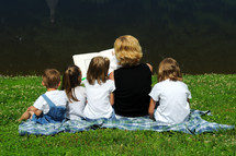 Woman reading a book to children, sitting on the grass on a blanket