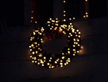 Christmas lights on a wreath - A Christmas Wreath decorated in Christmas white lights and red ornaments lights up the night in the background giving the night light to spread the joy of Christmas.