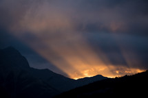 rays of light behind a mountain at sunrise