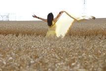woman dancing in a field of wheat
