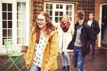 teens walking out a backdoor onto a courtyard