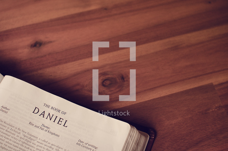 BIble on a wood floor opened to Daniel