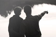 father with his son pointing at the water of a lake