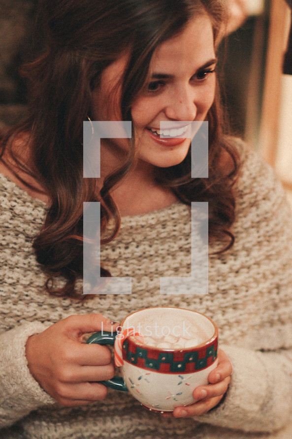 happy woman holding a mug of hot cocoa