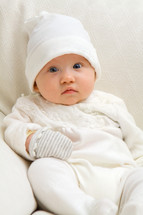 sitting baby dressed in white