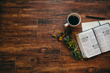 open Bible, journal, pen, earbuds, iPhone, and flowers on a table