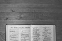 Bible on a wooden table open to the Song of Solomon.