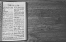 Bible on a wooden table open to the Letter of Paul to the Colossians.