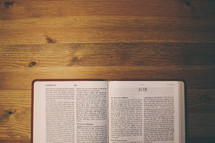 Bible on a wooden table open to the book of Job.