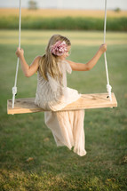 A young girl sitting on a swing