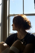 profile of a woman sitting in a a window