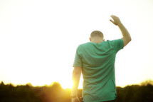 A man, with hand raised, worshipping at sunrise