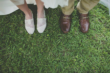 two pairs of feet in shoes standing in the grass after their wedding