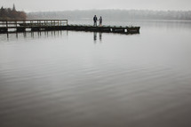 man and woman standing on a dock holding hands