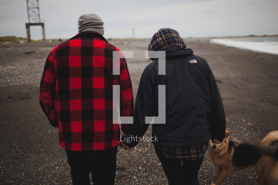 couple walking dog on a cold day