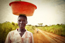 African woman carrying bucket on head.
