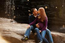 man kissing a pregnant woman sitting on rocks