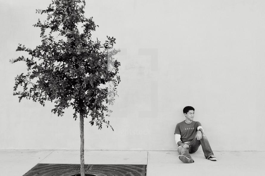man sitting on a city sidewalk