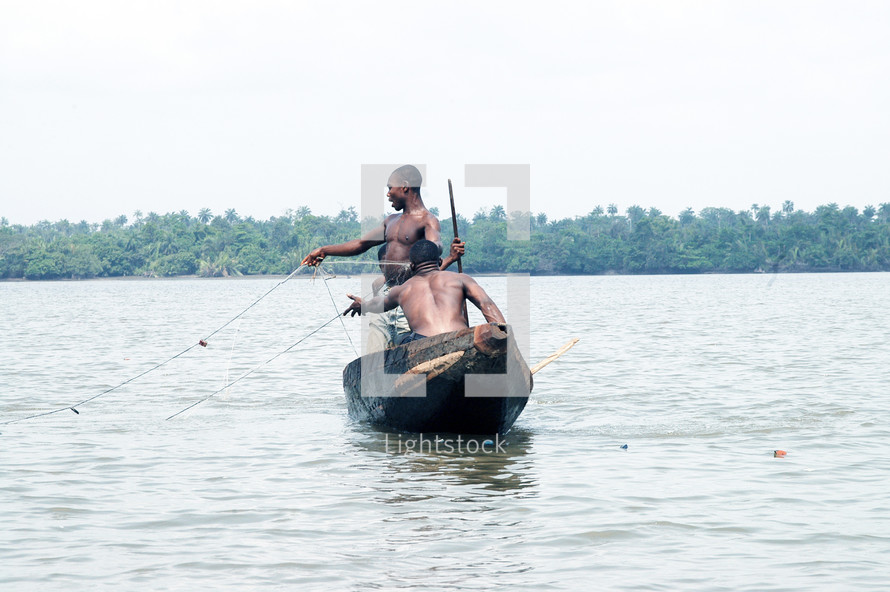 A pair of Nigerians fishing from a dug-out canoe.