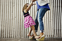 Girls walking on her mother's shoes while holding hands.