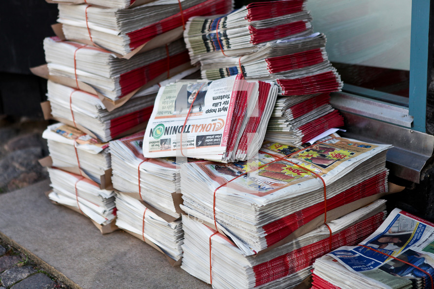 Stacks of newspapers tied up on the ground