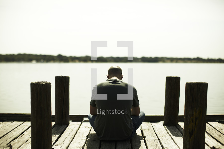 A man sitting and praying on a dock