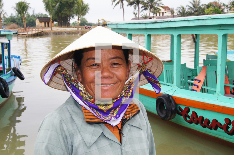 Vietnamese woman in straw hat in front of water taxi's (For more like this, try also search for 'Ethnic Face')