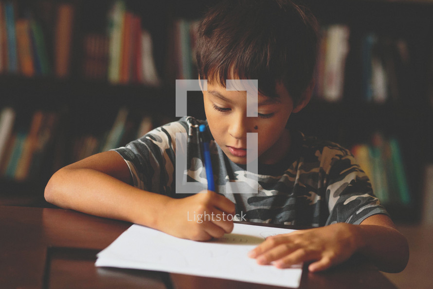 A young boy writing on a sheet of paper