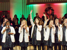 A group of female and male singers sing a chorus of praise during a Christmas praise and worship concert wearing white blazers and sparkling dresses while singing during a church Christmas concert. These are the voices of Mobile - a praise and worship group from Mobile Alabama singing at a Christmas concert along with the church choir at a recent praise and worship event.