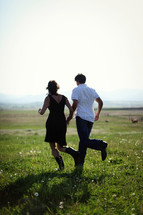 Man and woman in boots running across grassy field.