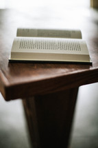 Open bible sitting on wooden pulpit
