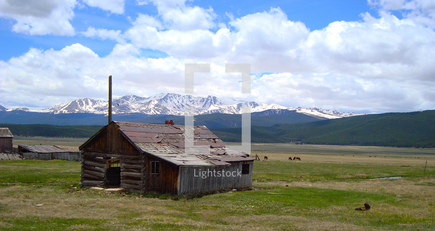 Log cabin in a field surrounded by mountains