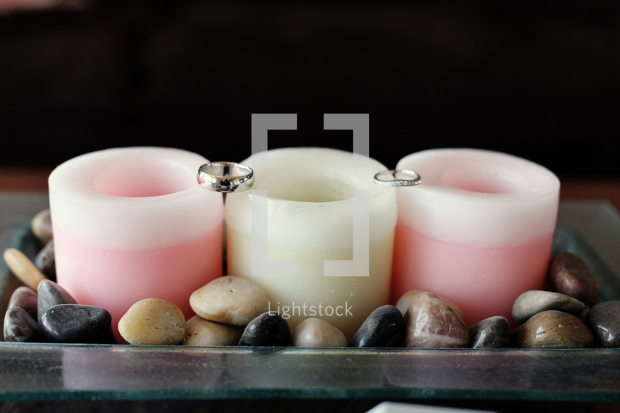 Wedding rings sitting on candles