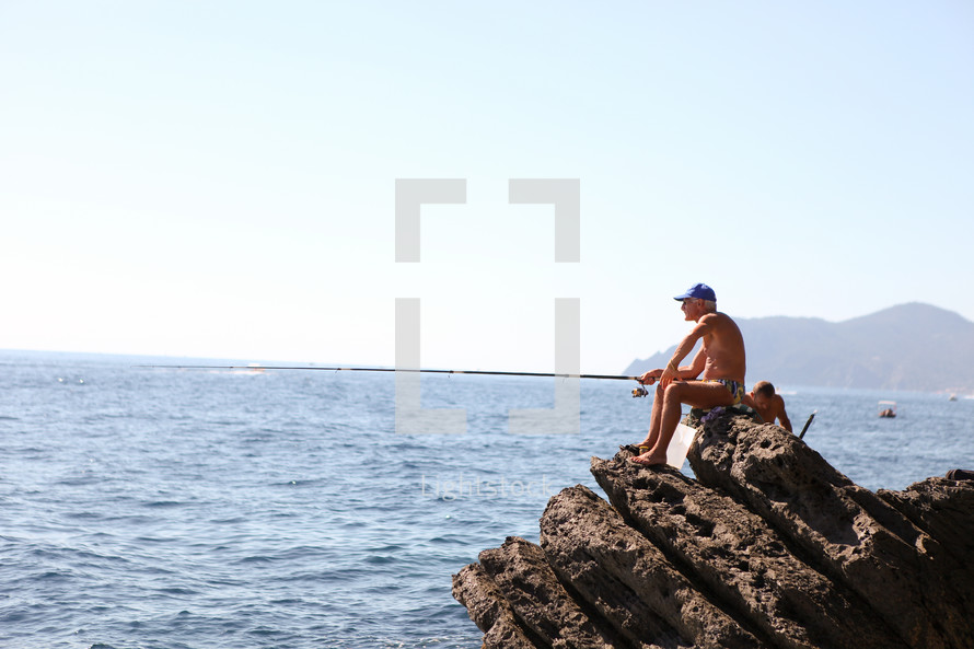 A fisherman sitting on a rock fishing