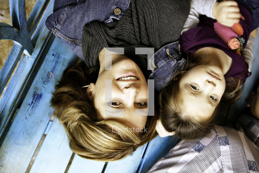 Mother and daughter lying on a bench