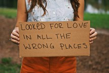 woman holding a sign with the words LOOKED FOR LOVE IN ALL THE WRONG PLACES