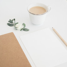 coffee with creamer, paper, and pencil