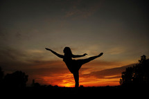 girl in ballet poise against sunset