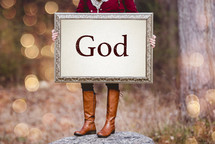 a woman holding a sign the reads God