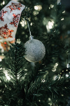 silver glittery ornament on a Christmas tree