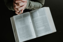 a woman praying over a Bible