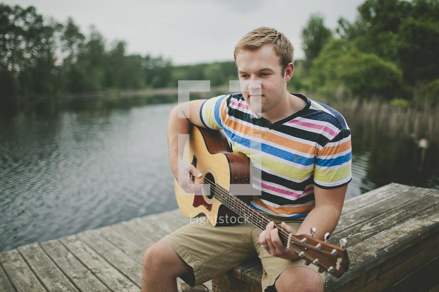 Man playing guitar on river deck