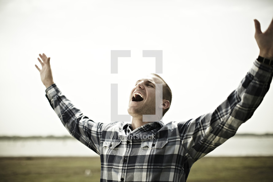 Young man worshipping with hands raised near lake.